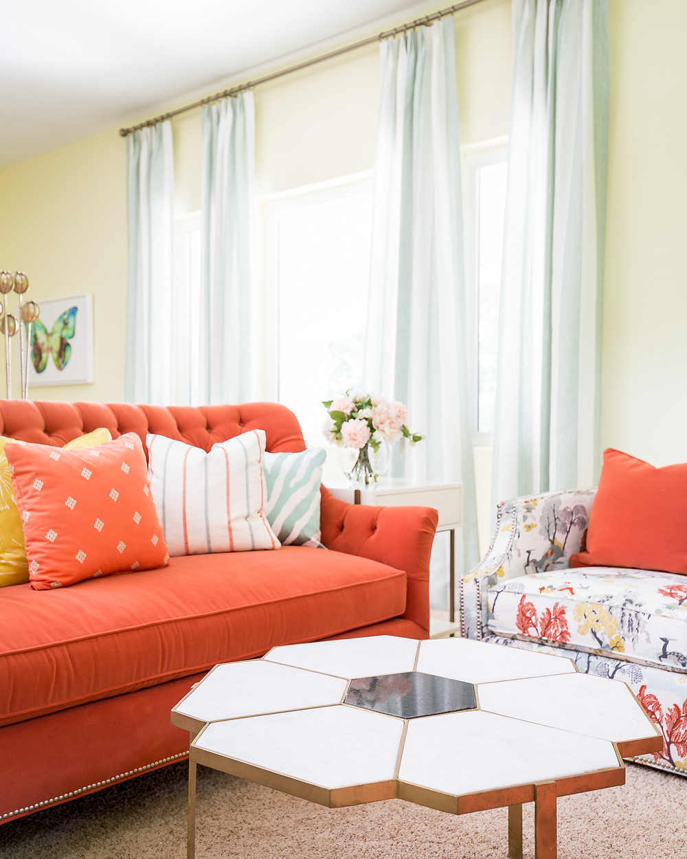 Coral sofa with yellow walls and striped draperies