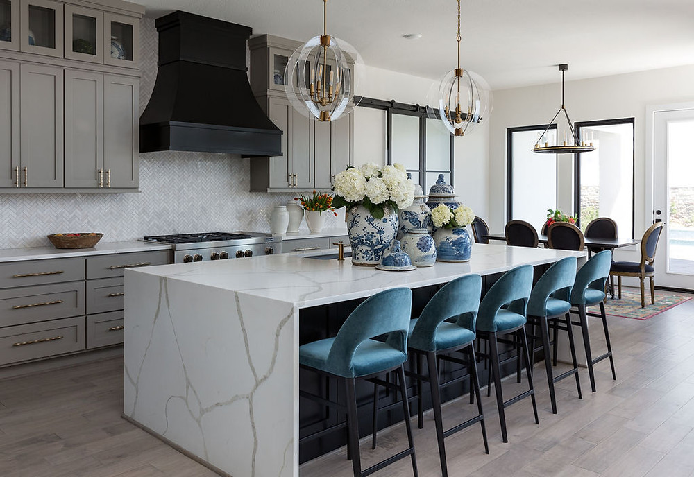 Modern Kitchen With Quartz Waterfall Countertops and Black Range Hood
