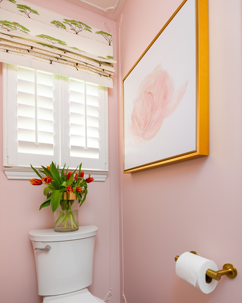 gold framed art in powder room with blush walls