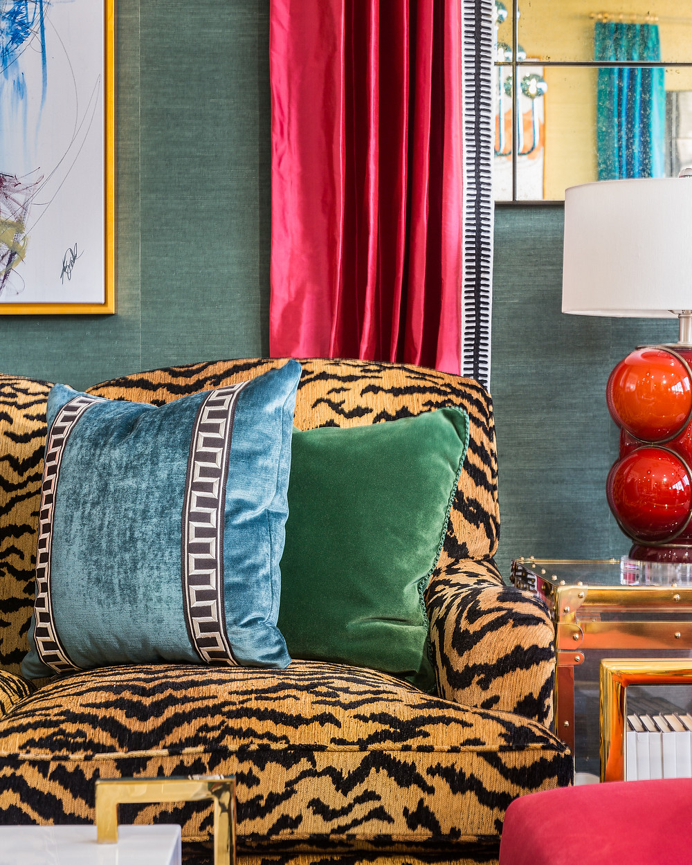 Tiger striped sofa with silk draperies and green grasscloth wallpaper