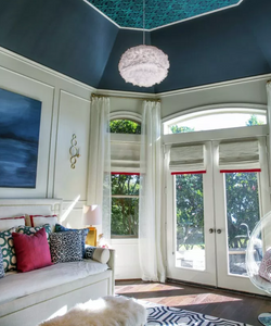 Grasscloth wallpaper in vaulted ceiling in bedroom with navy blue paint