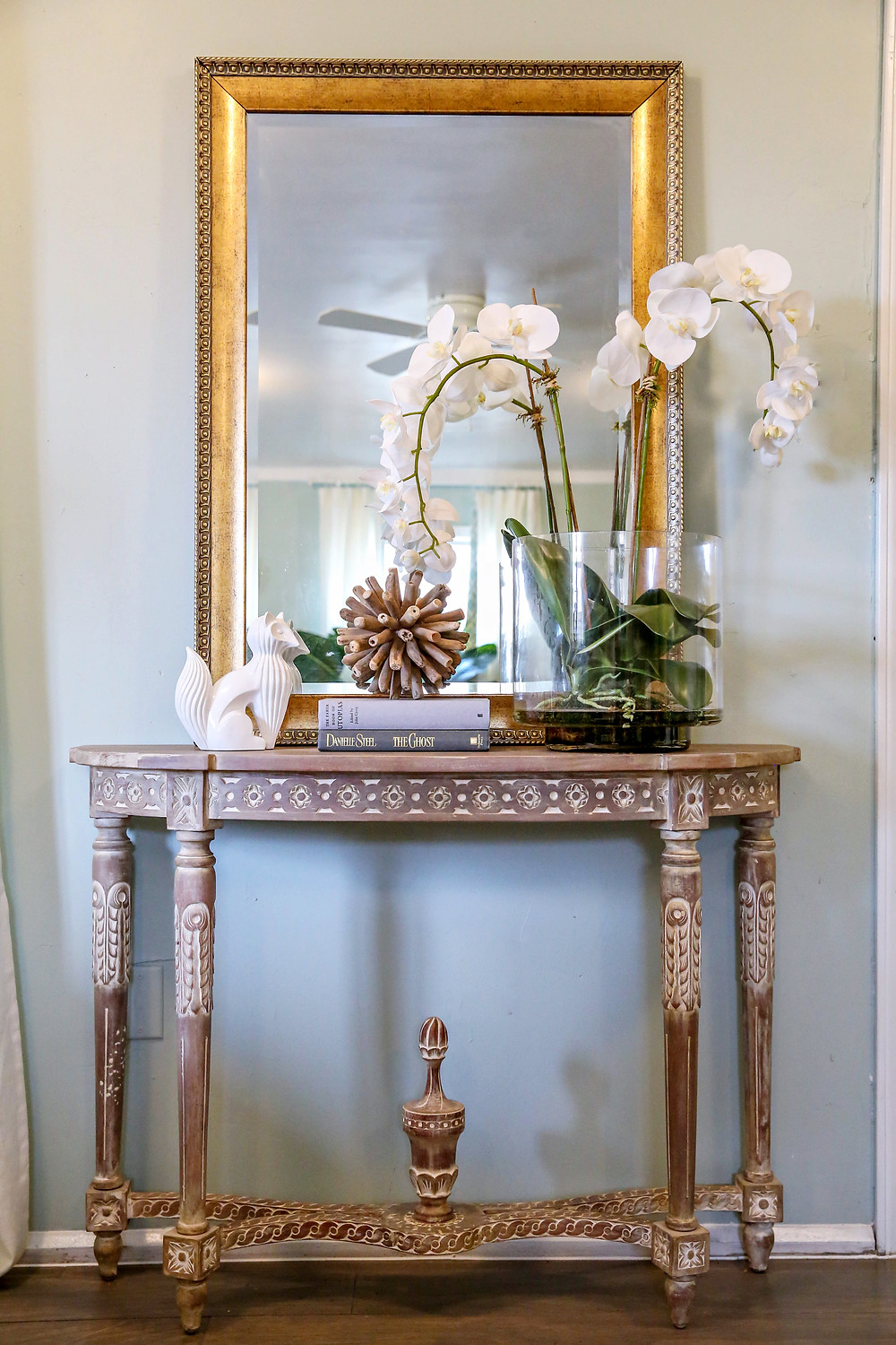 Foyer table with gold mirror and orchid floral arrangement