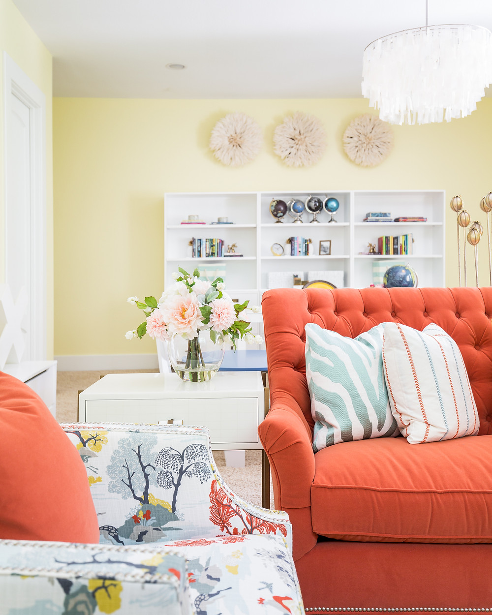 Soft yellow walls with coral velvet sofa