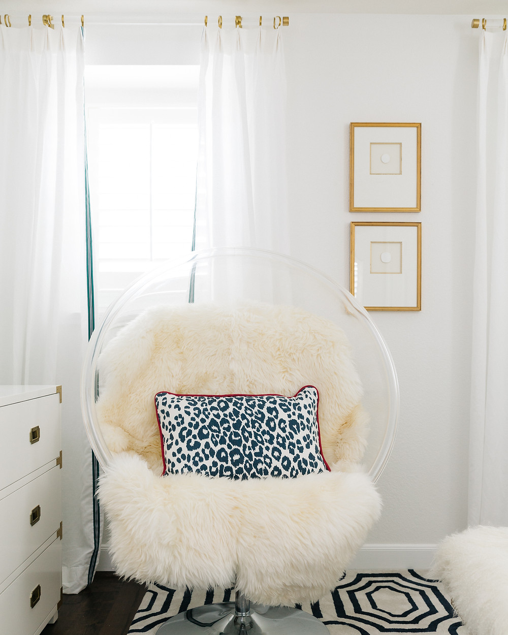 Acrylic bubble chair with lambs wool rug, white walls with white draperies