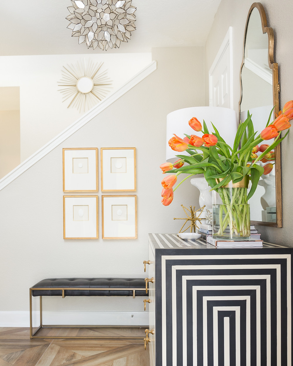 Foyer with black and white chest and vase of orange tulips