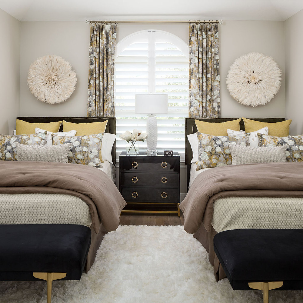2 Full size beds in a guest bedroom with custom bedding, upholstered headboards, juju hats as wall decor, shag carpet and black velvet benches at the foot of each bed