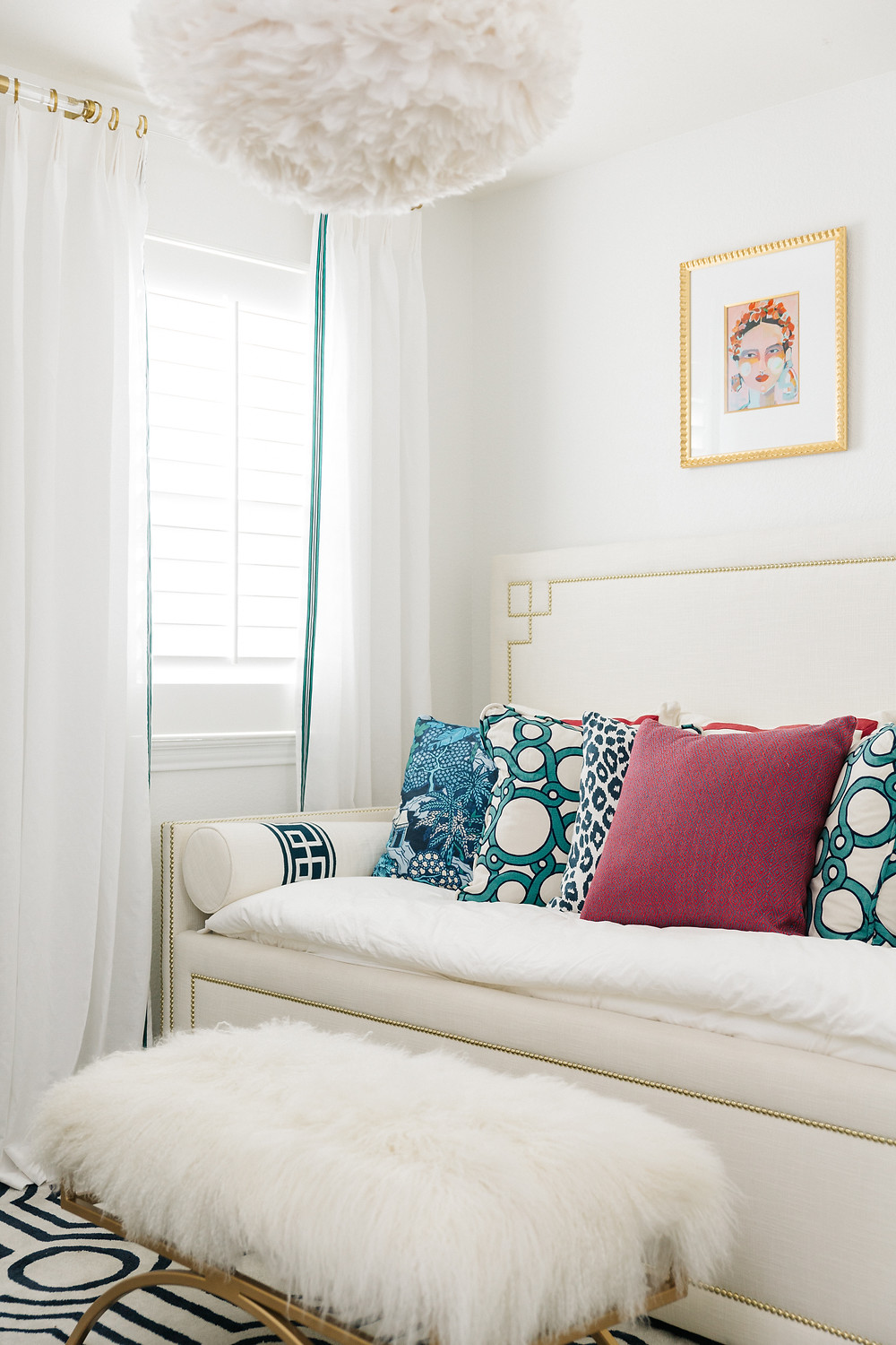 Guest Bedroom With White Walls, White Furnishings And Pops Of Color In Pillows