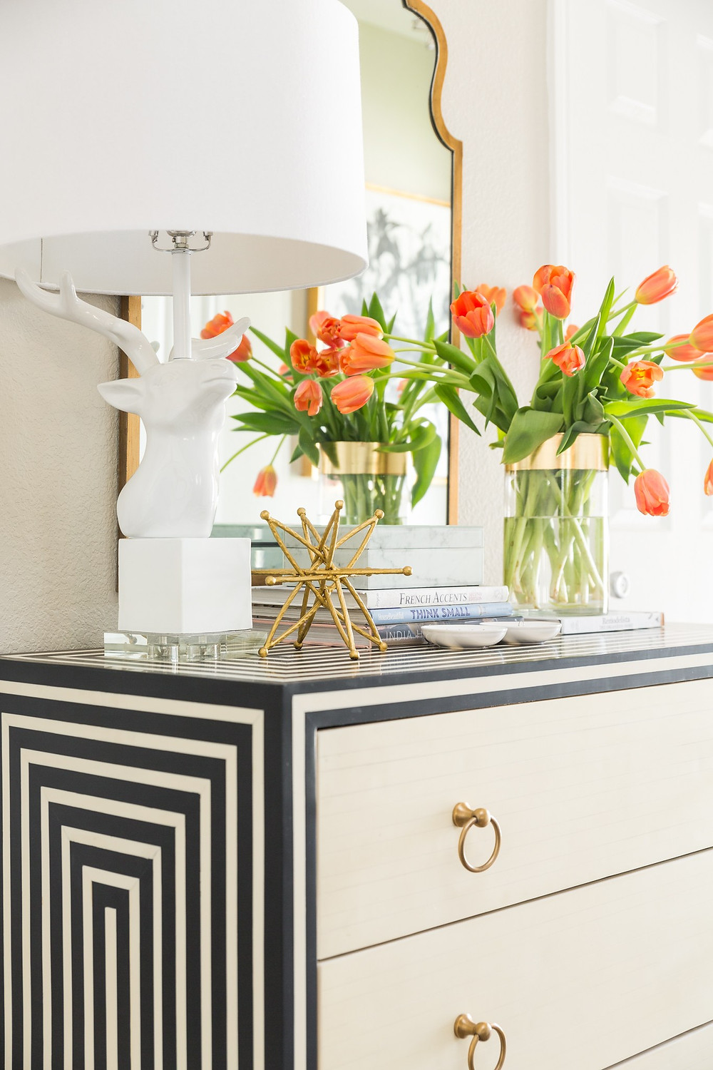 Foyer with black and cream chest and orange tulips