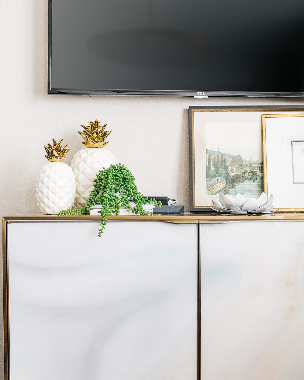 Wall mounted TV with vignette of art and greenery