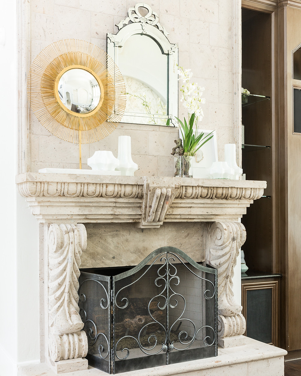 Stone fireplace with mirror and gold accent sunburst