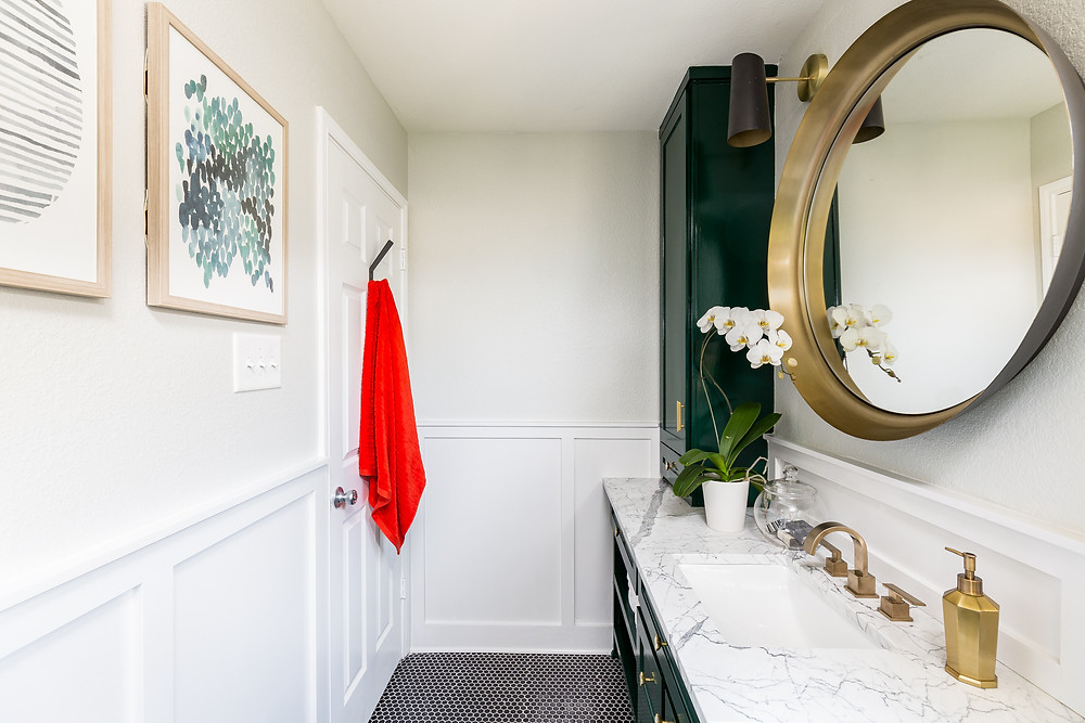 Guest bathroom with green cabinets, black mosaic floor, and chair rail molding