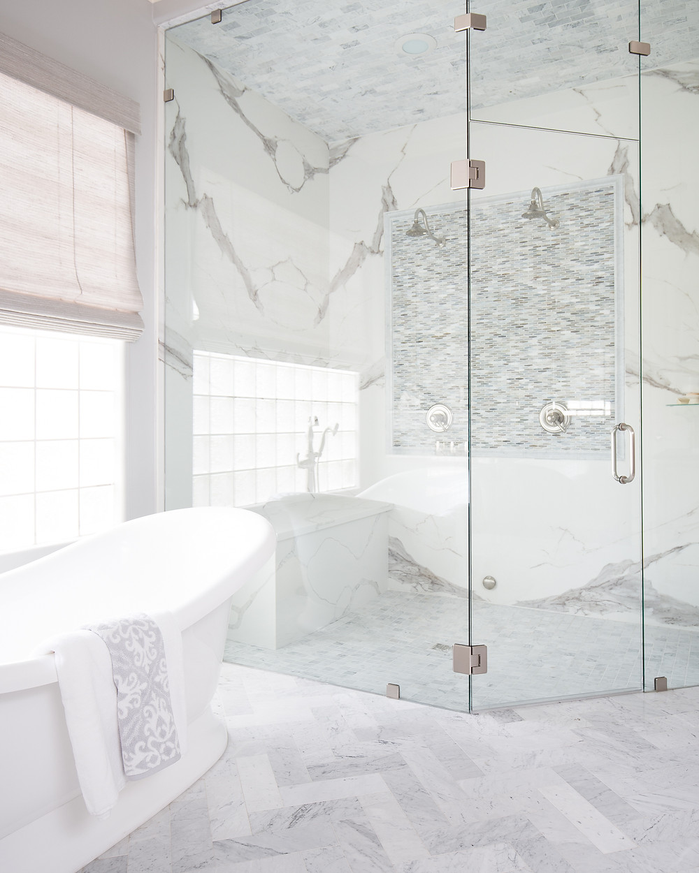 porcelain slab master shower with dual shower heads and mosaic accent tiles in marble