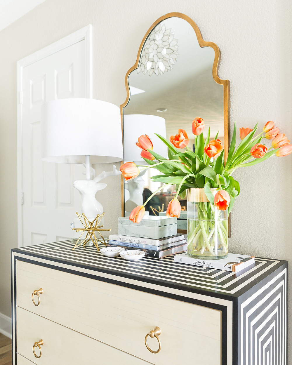 A foyer with chest and mirror and  orange tulips