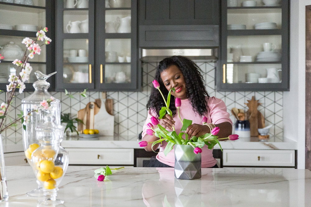 Veronica Solomon arranging pink tulips in her newly remodeled kitchen