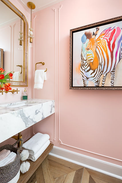 French inspired powder room with pink walls and moldin detail and marble countertop