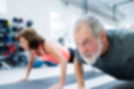 Senior couple in gym working out, doing