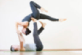 Man and woman doing acro yoga or yoga wi