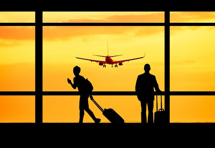 Due viaggiatori attendono il loro aereo