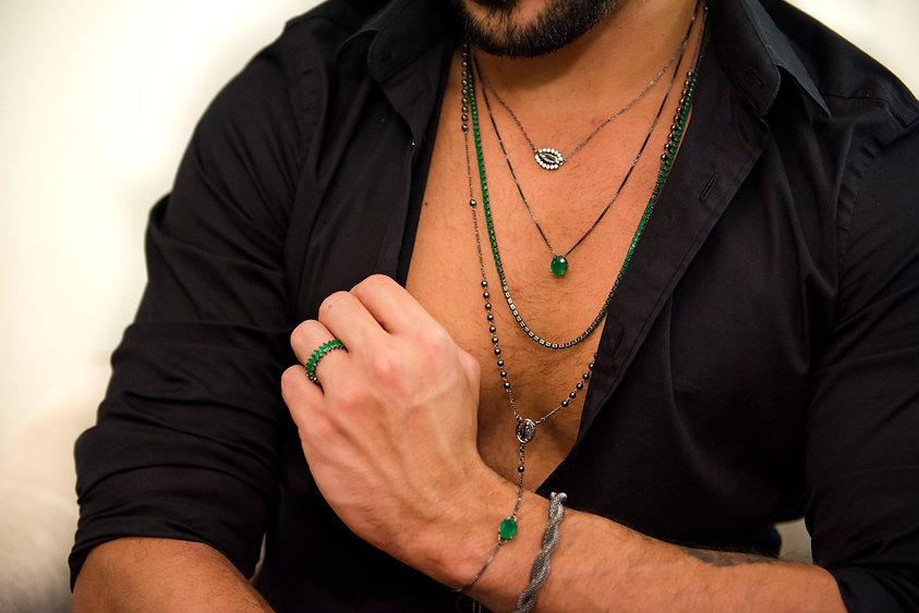 Rapaz utilizando vários acessórios masculinos como anéis, pulseiras, colares