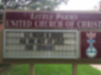 "The image is of the external signage at  Little Farms United Church of Christ. The sign has a red border and the UCC crest on the right side. The sign reads ""We wear a mark as an act of love for others!"" in black lettering"