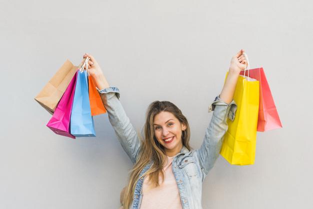 joyful-woman-standing-with-shopping-bags