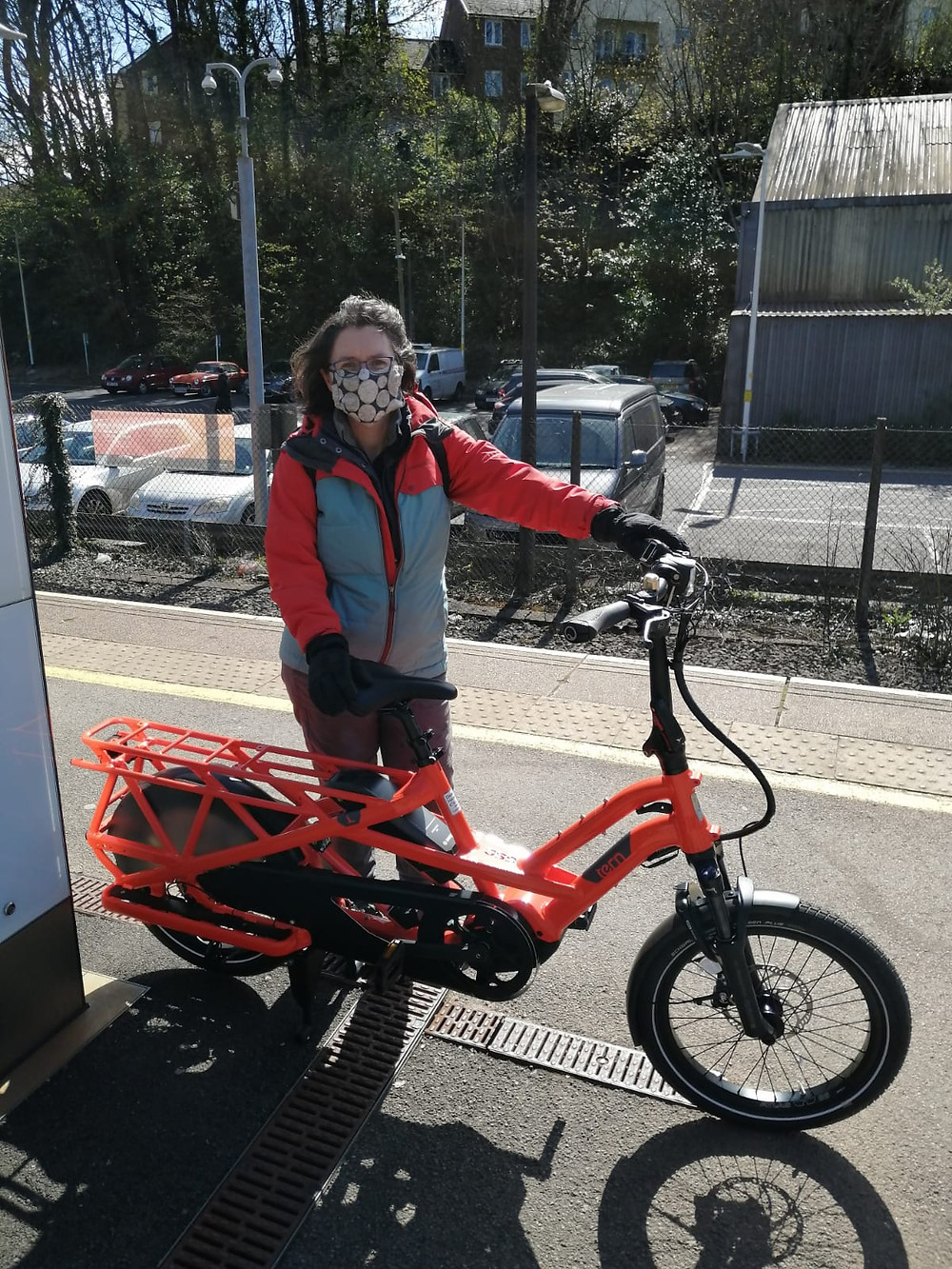 Person standing behind a bicycle holding the seat and handlebars. They are on a grey platform at a railway station. The person has shoulder length brown hair, a black and brown facemask on and blue glasses. They are wearing a red and blue zipped rain coat and grey tight fitting trousers. The bike is bright orange and has a frame that extends to a rack at the back.