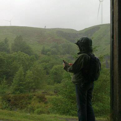 Rainy scene with an artist in green weatherproofs and rugged mountain with wind turbines