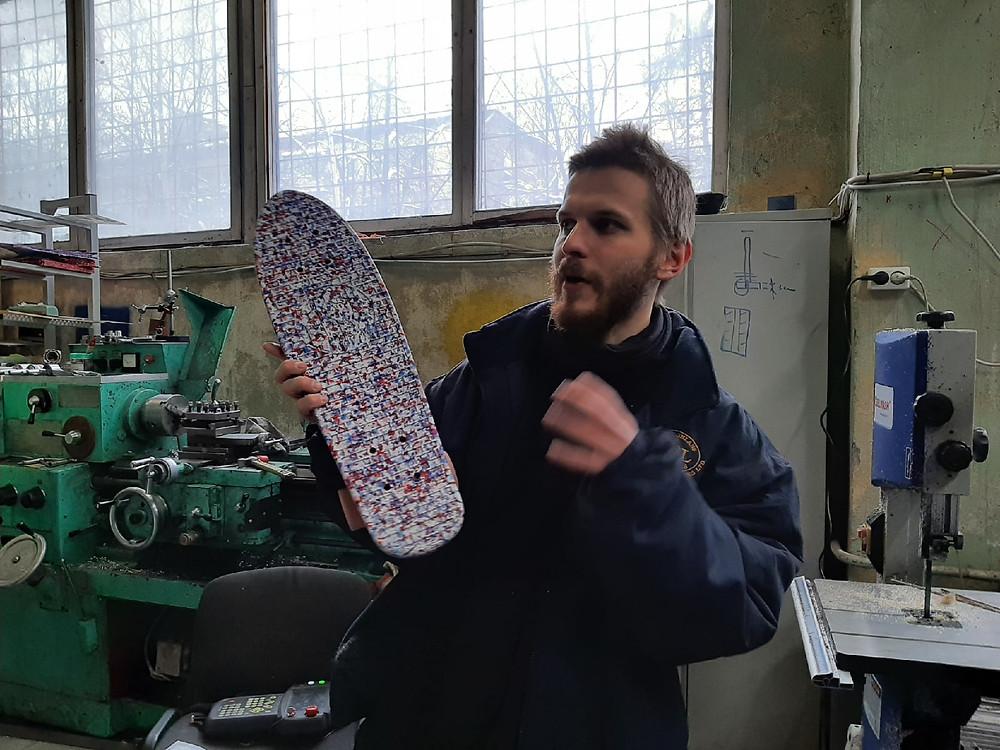 Саша Семенов, сооснователь компании 99recycle, держит в руках скейт, сделанный из переработанных пластиковых крышечек от бутылок