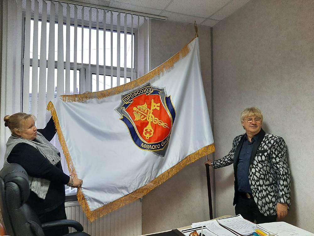 Герб на знамени содержит кадуцей, ключ и щит