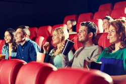 cinema, entertainment and people concept - happy friends watching movie in theater.jpg