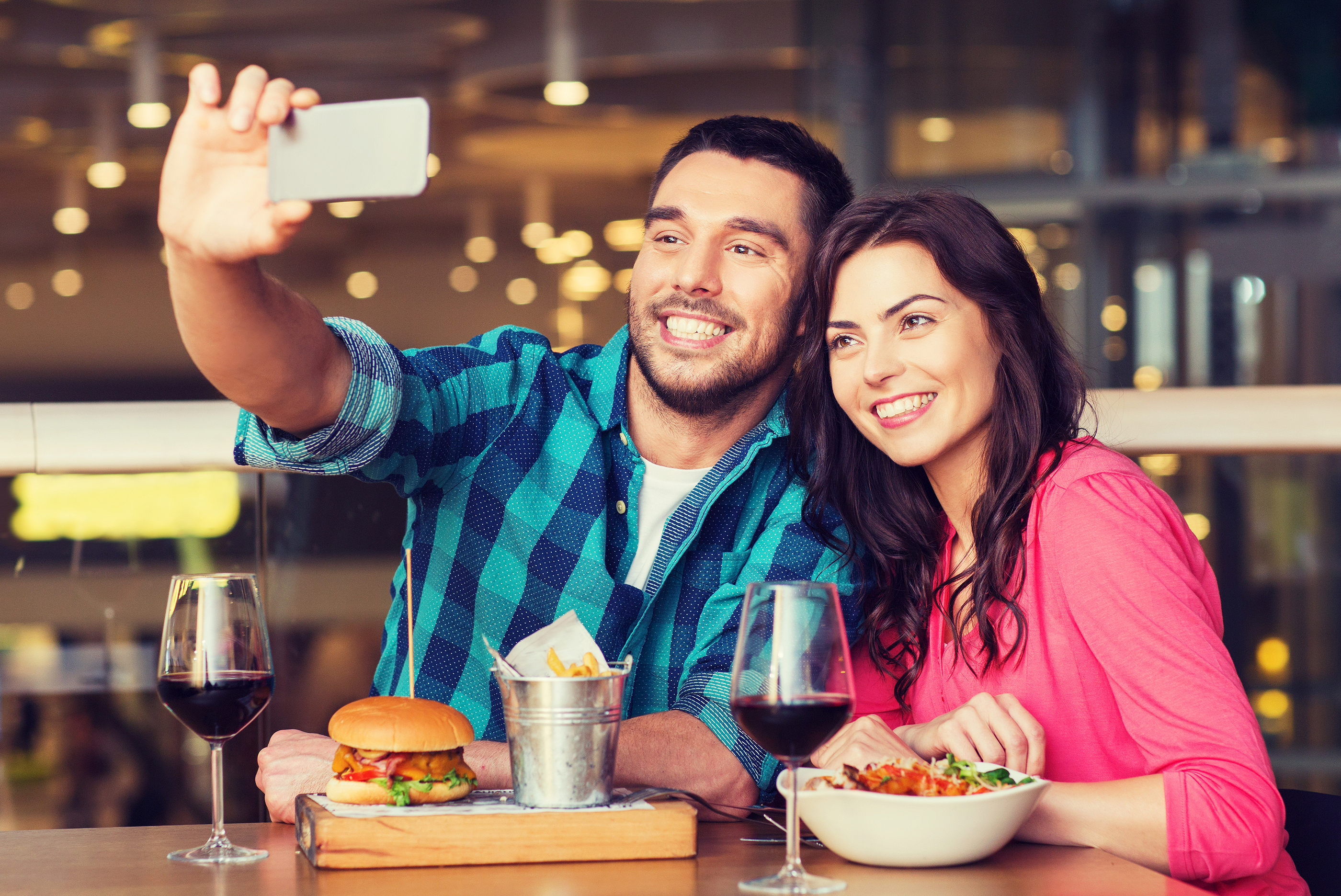 leisure, technology, date, people and holidays concept - happy couple having dinner and taking selfi