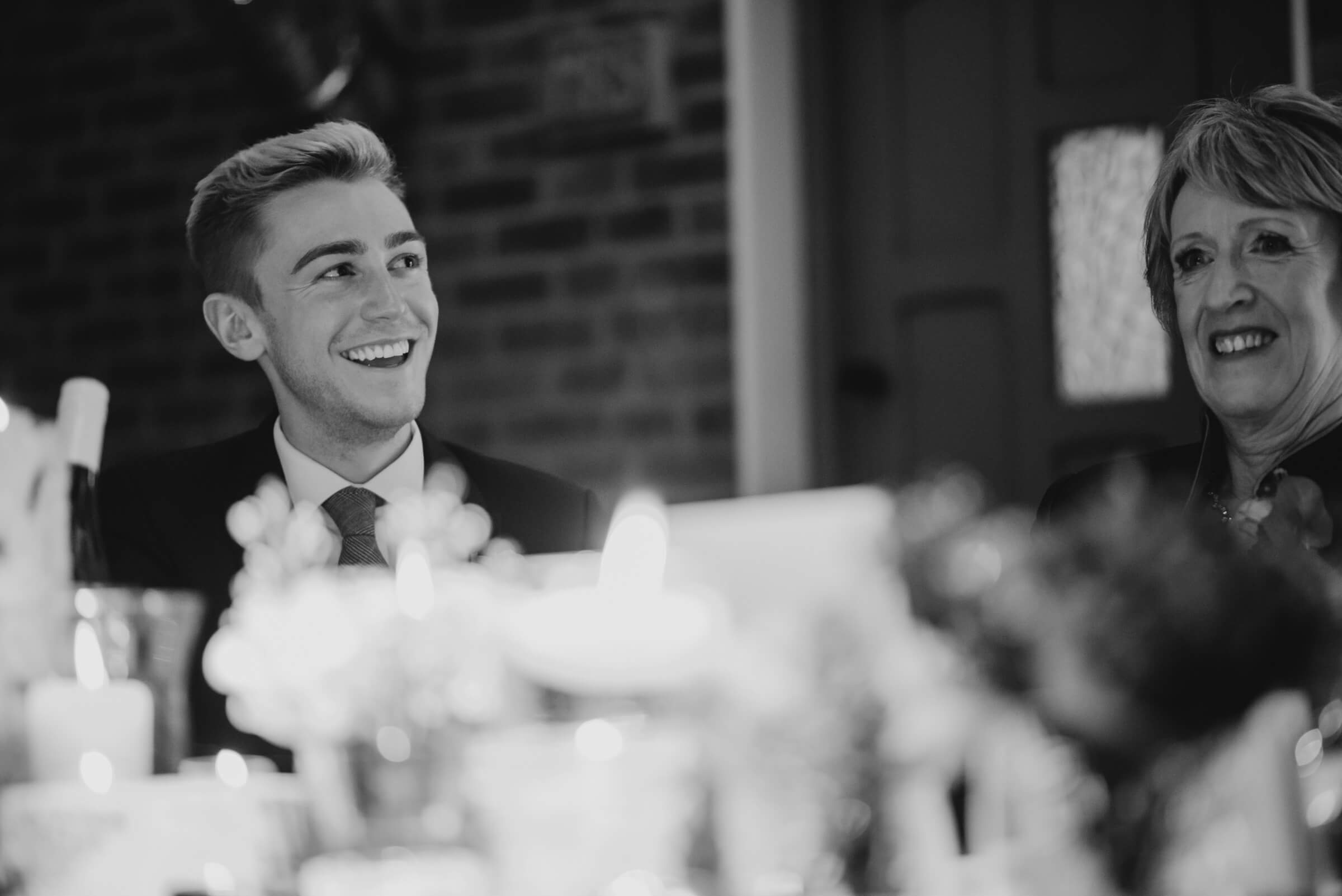brother of bride smiling during brides speech