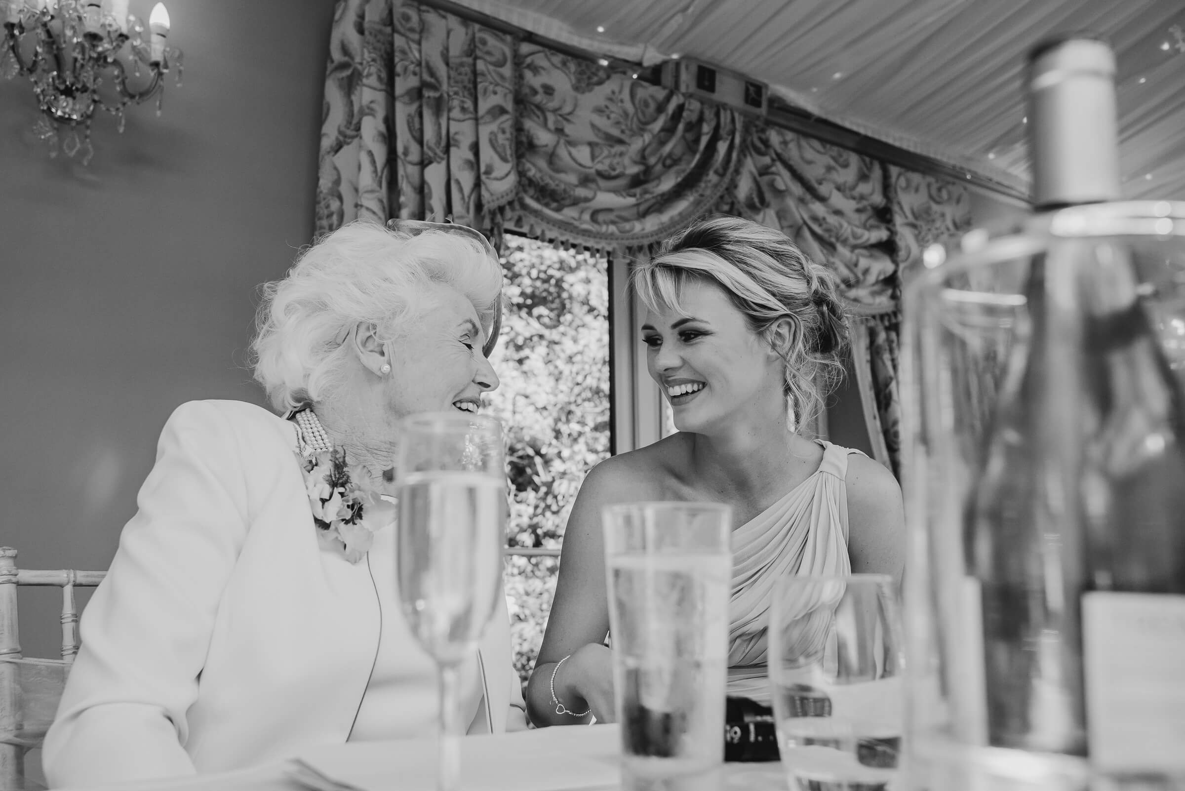 brides grandmother and bridesmaid laughing together