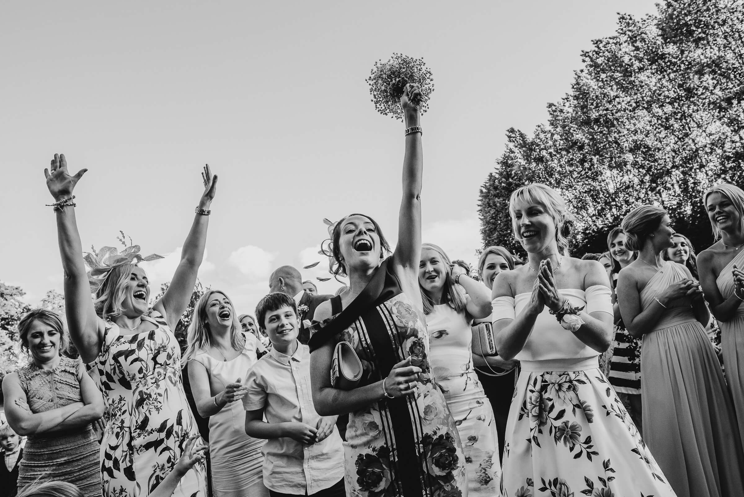 lady catching bouquet and holding it up in air
