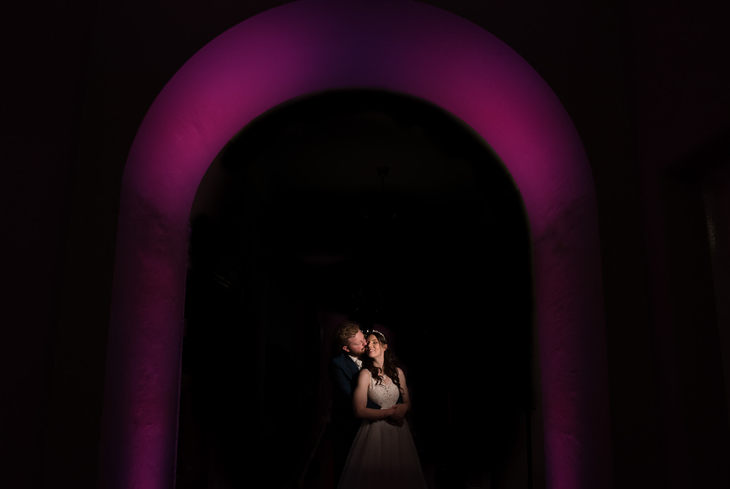 bride and groom holding each other under illuminated arch