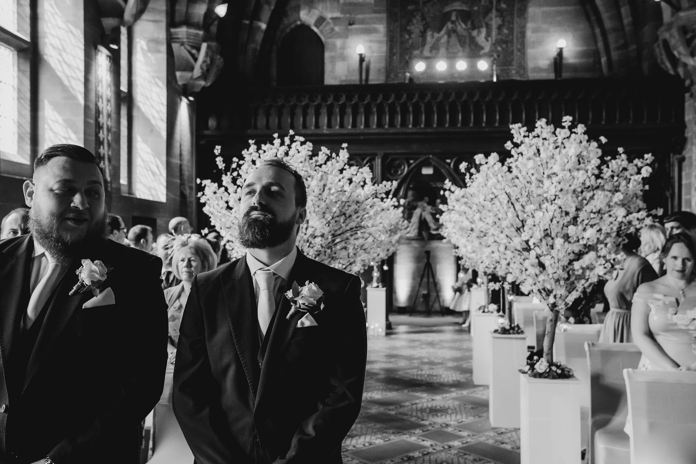 groom waiting at the top of the aisle