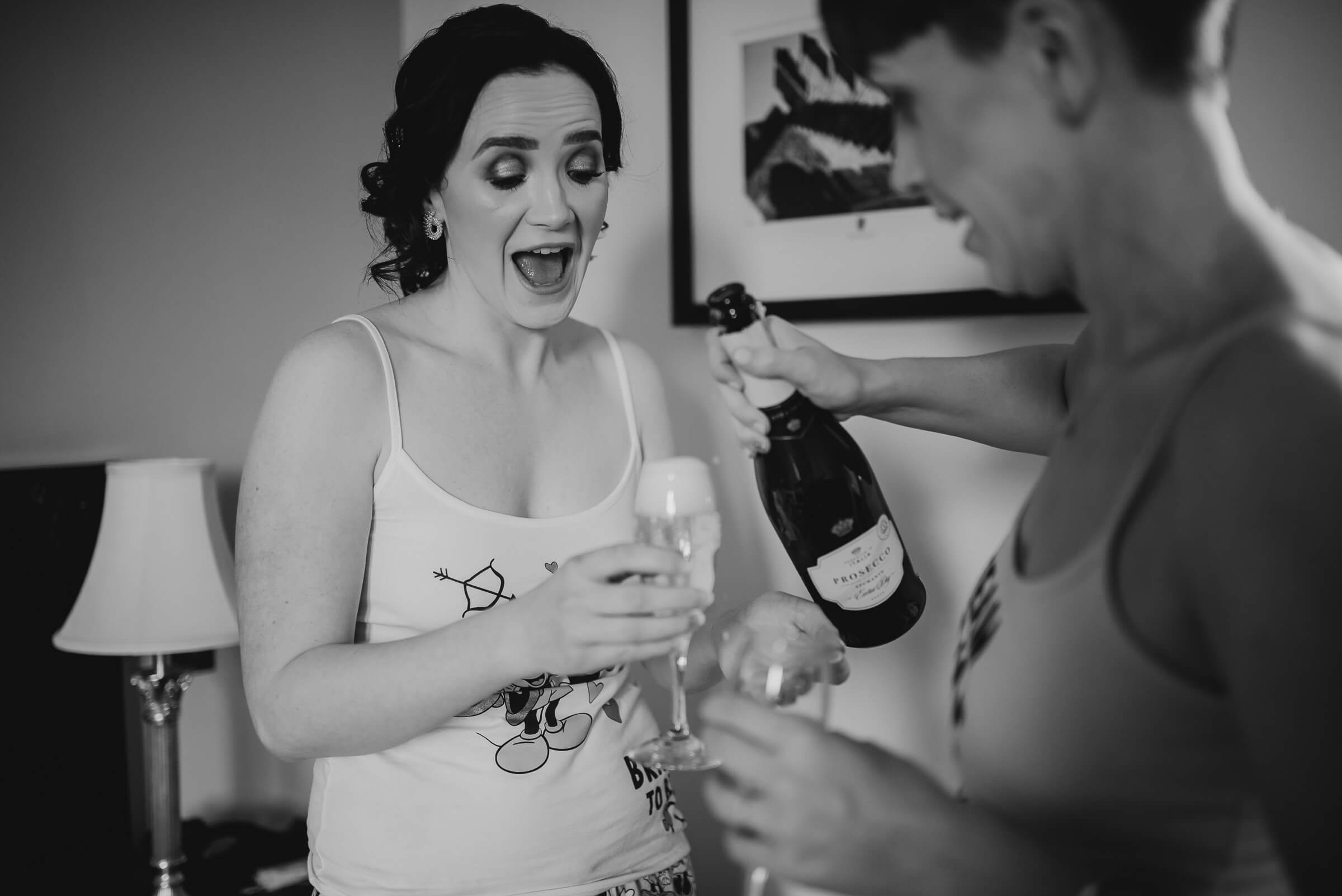 bride laughing while champagne being poured