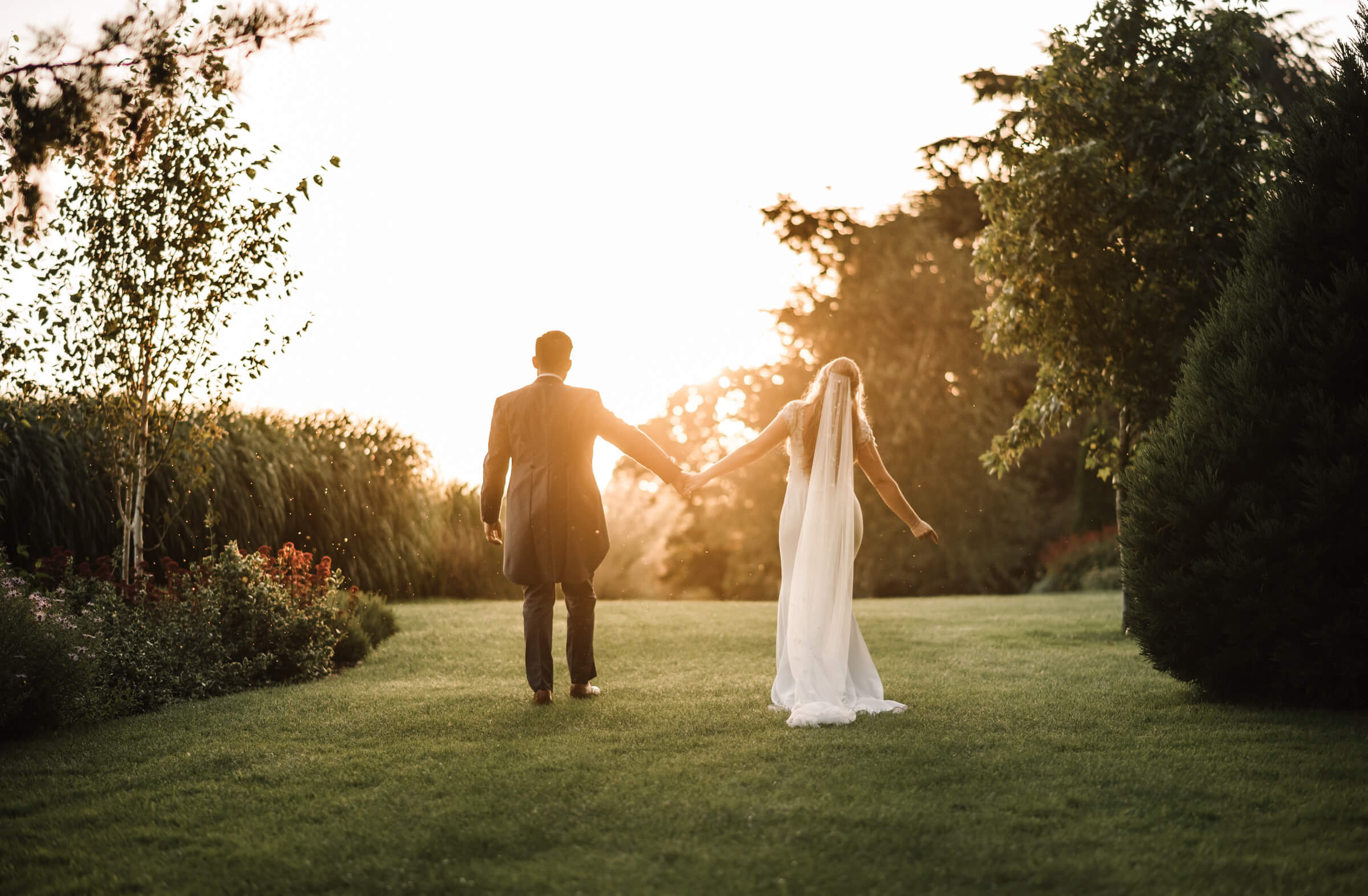 bride and groom walking into evening sunlight