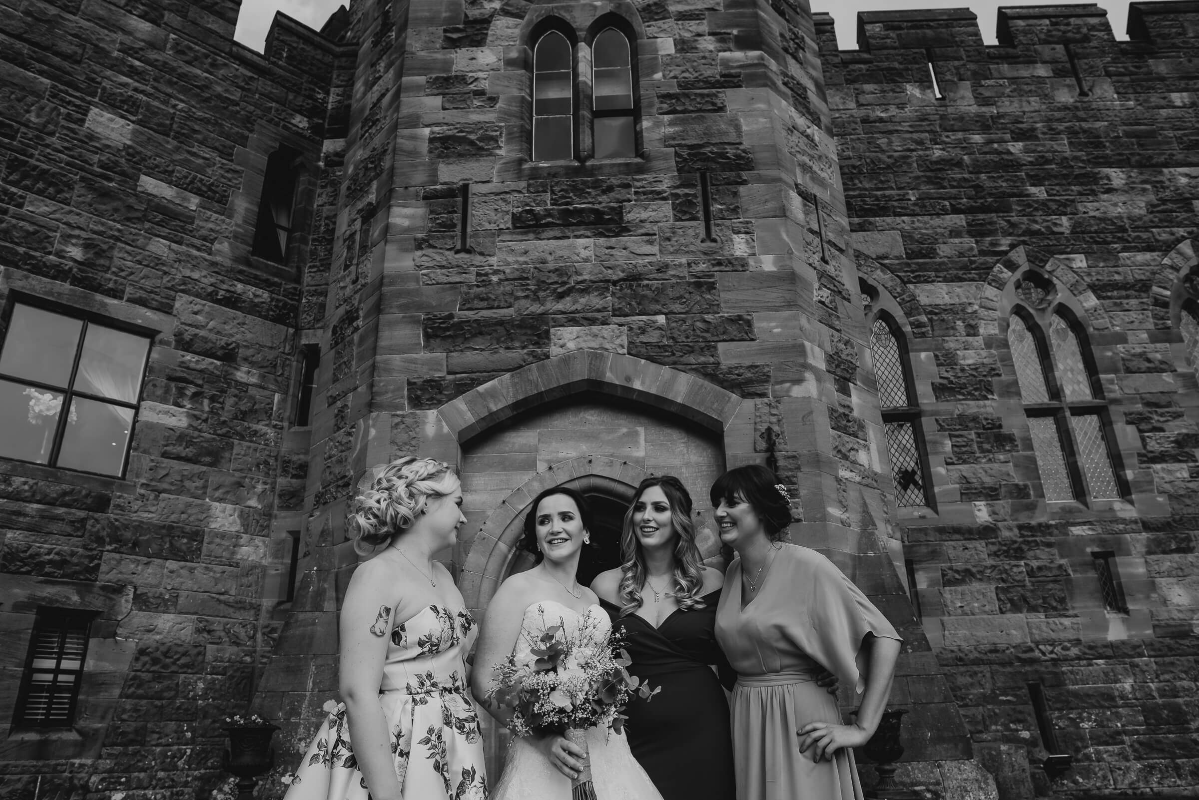 bride with bridesmaids against castle wall