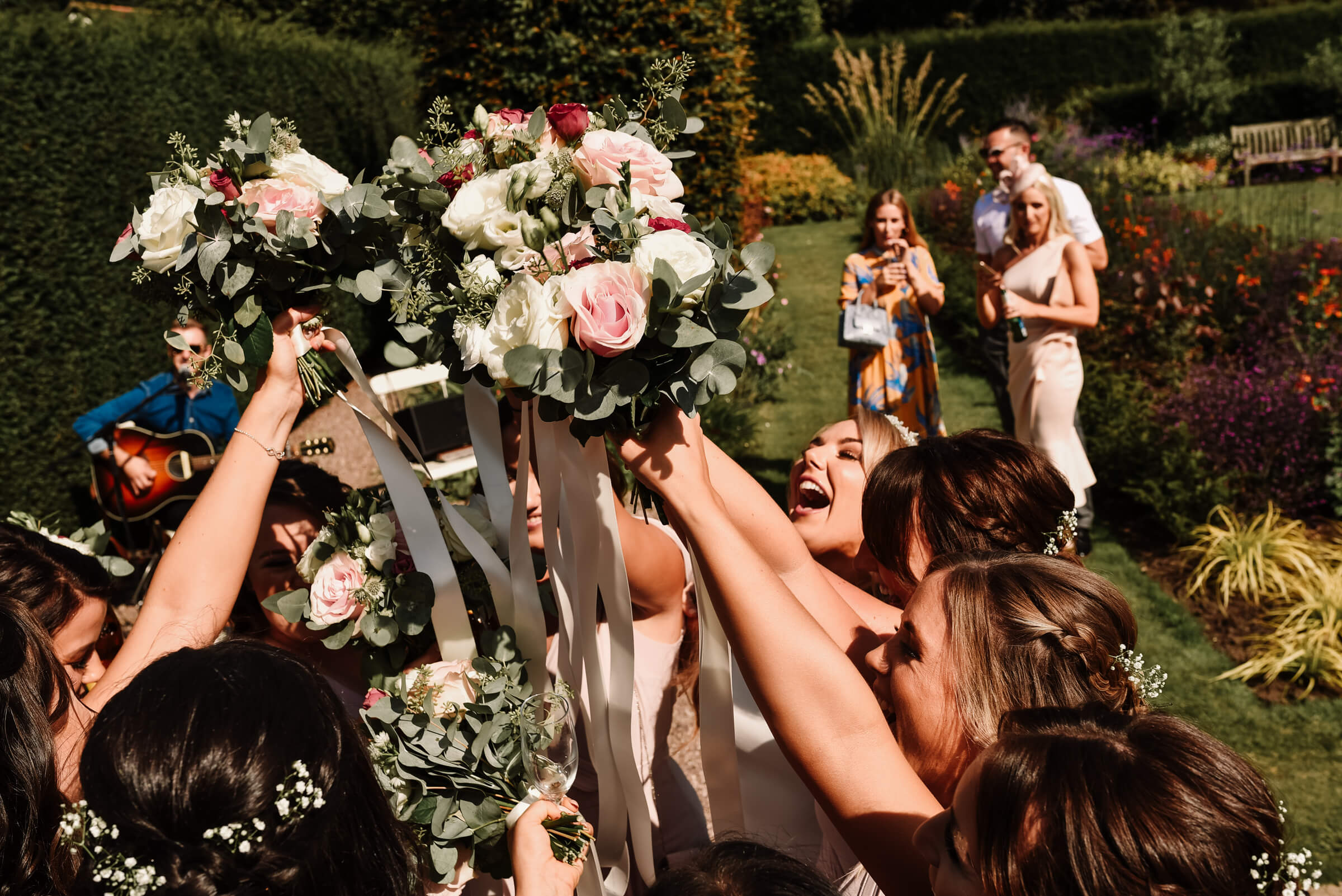 bride and bridesmaids holding bouquets in air and cheering