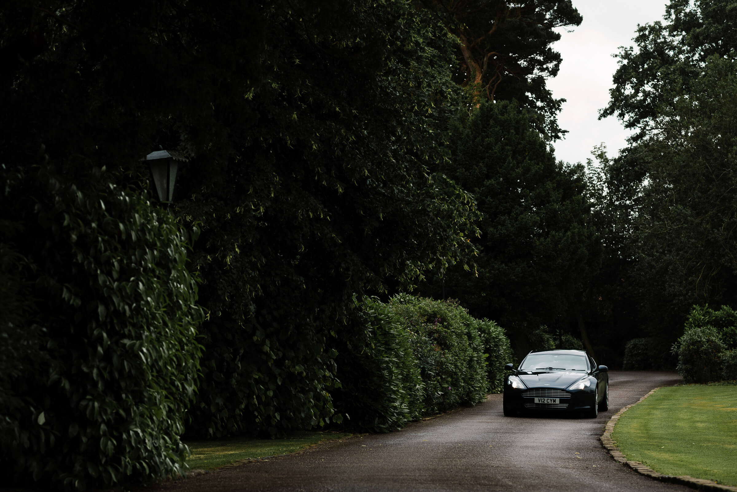 Wedding photography of groom arriving in aston matin