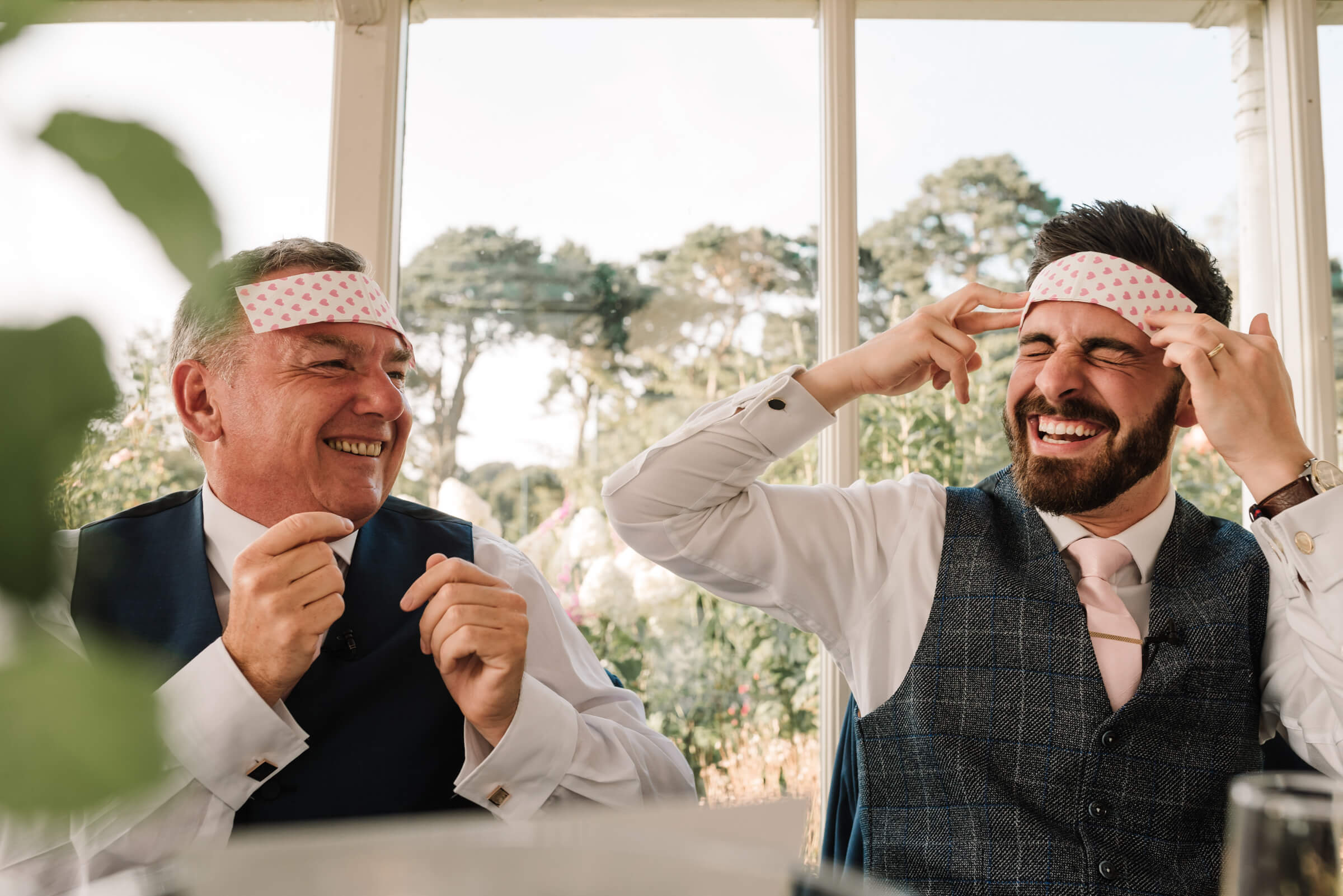 groom laughing with father of bride with cooling pads on head