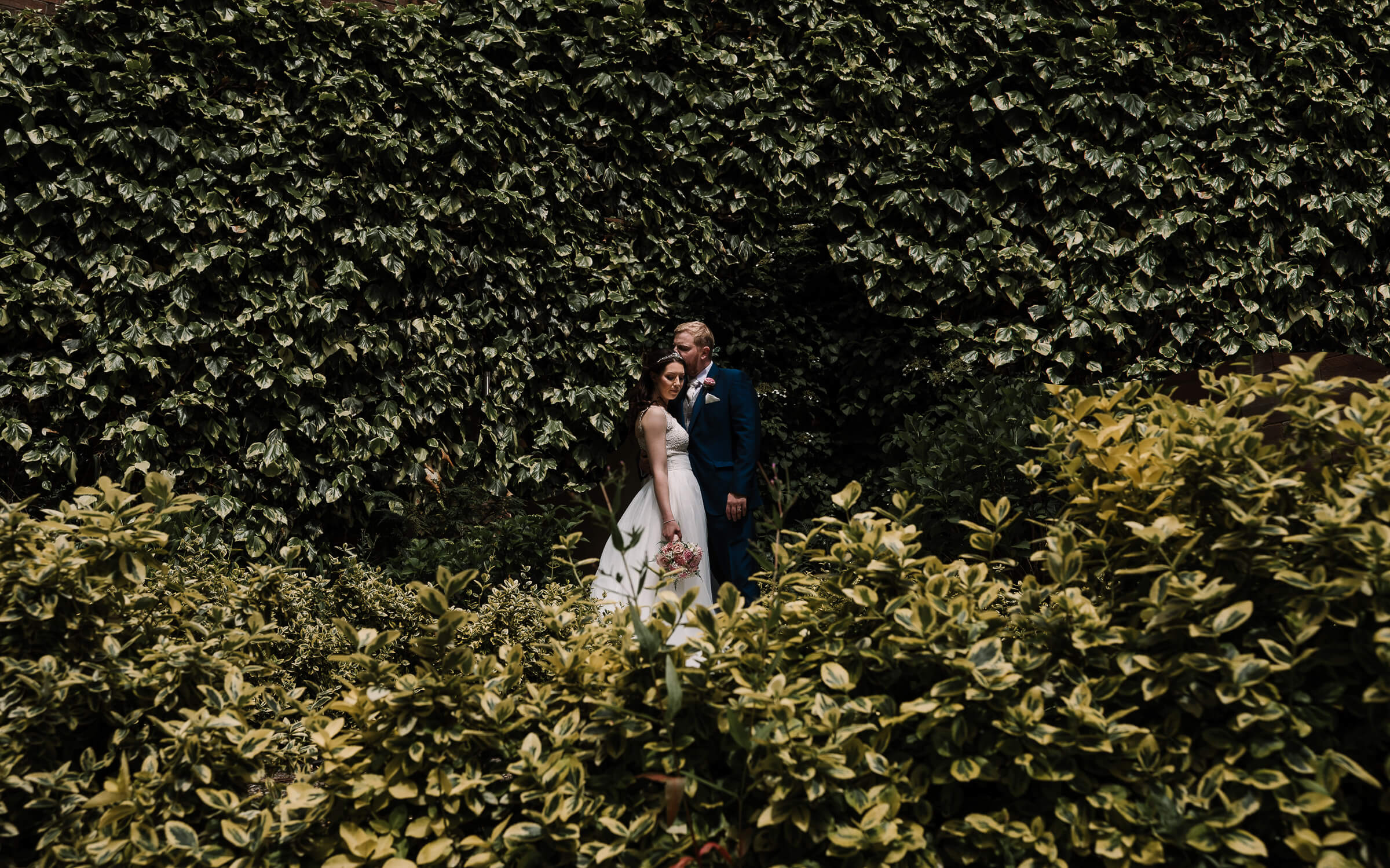 portrait of bride and groom surrounded by foliage
