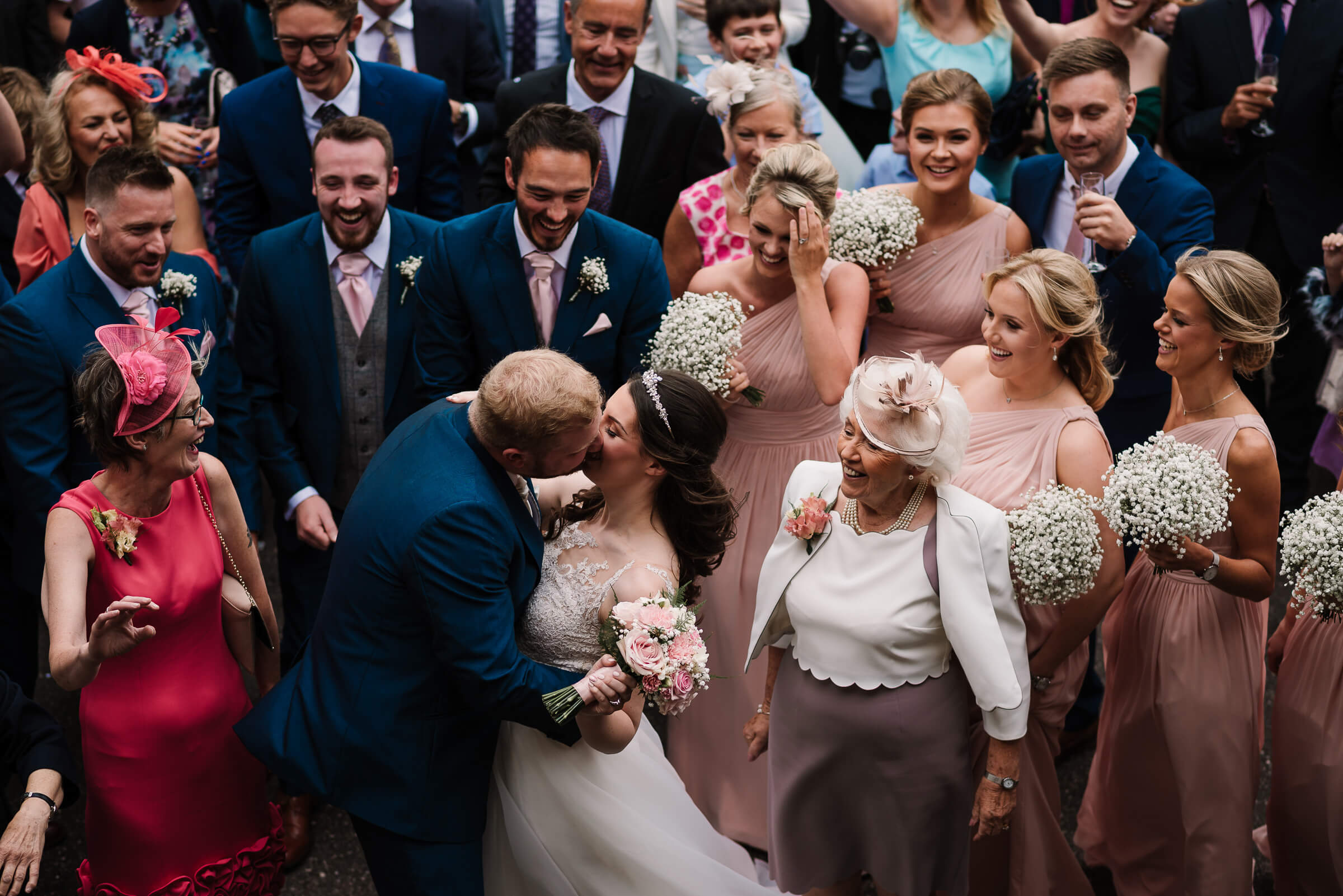 bride and groom kissing surrounding by guests