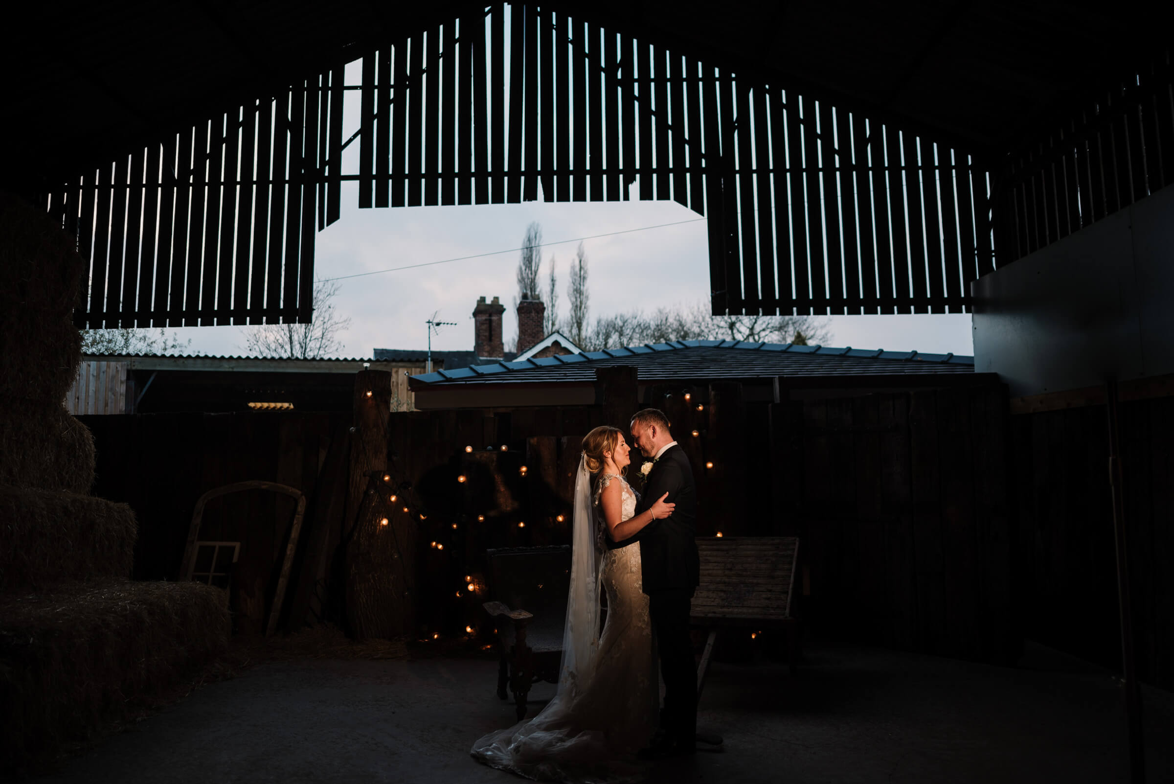 bride and groom against fairy light backdrop