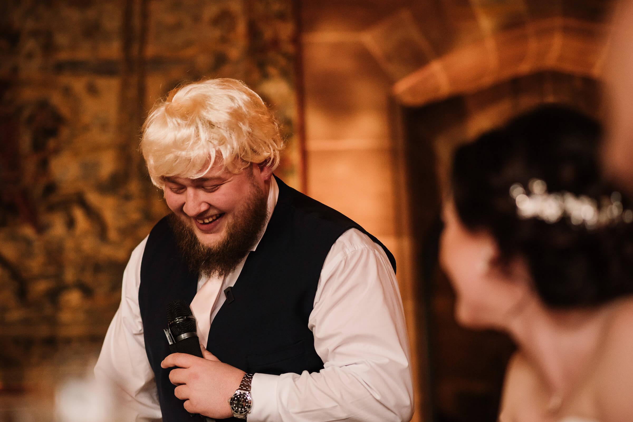 best man wearing blonde wig during speech
