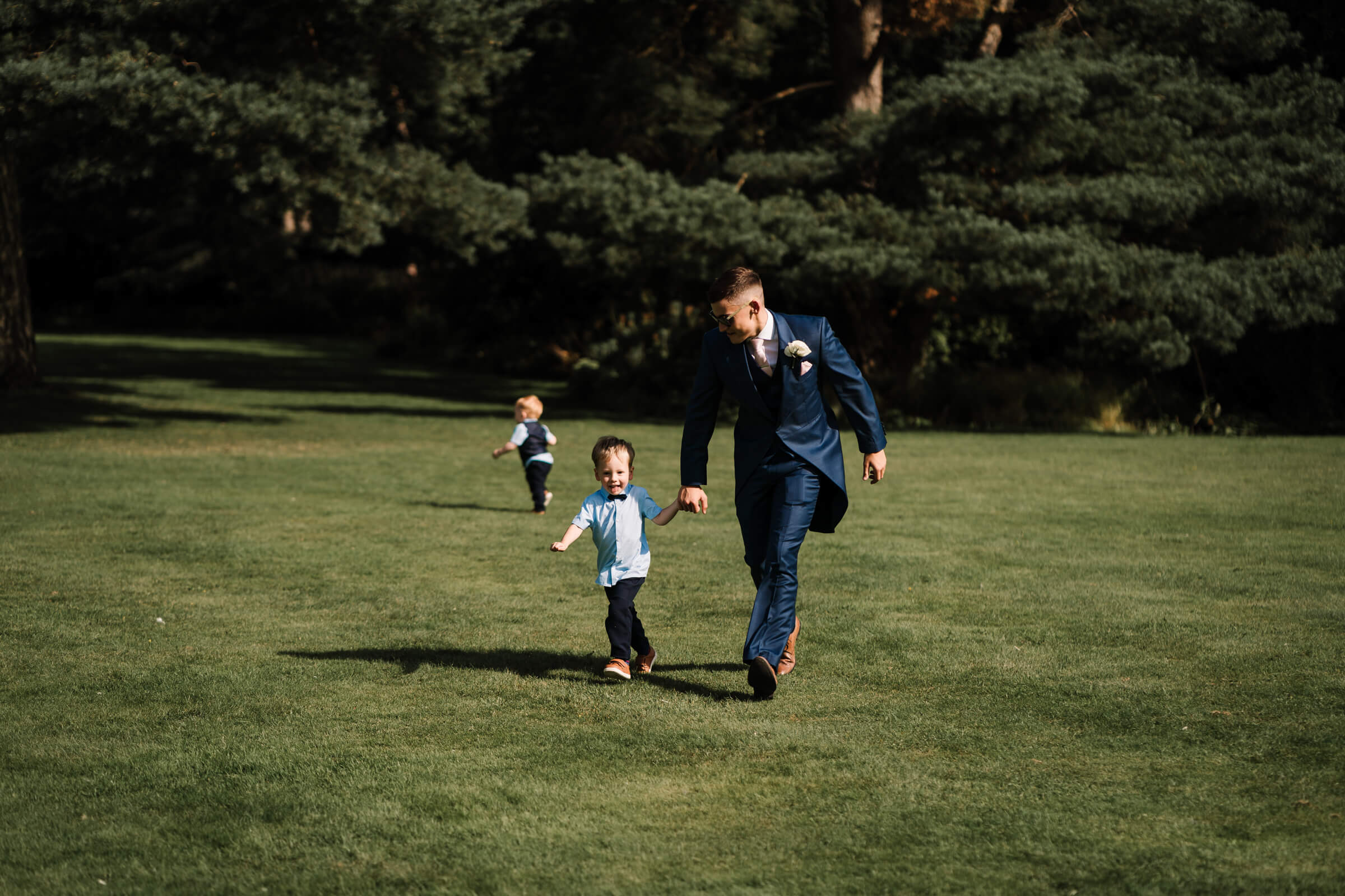 brother of groom running with you boy on lawn