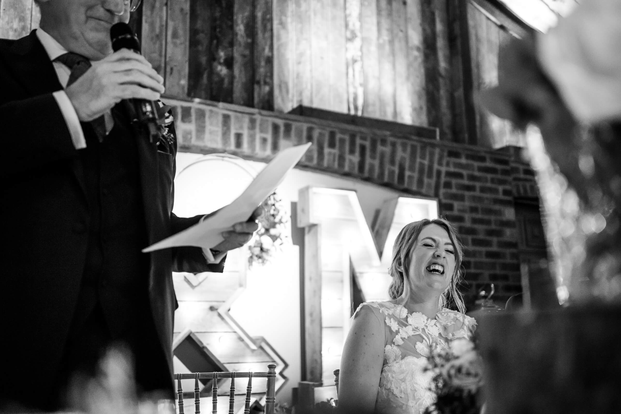 bride laughing during father speech
