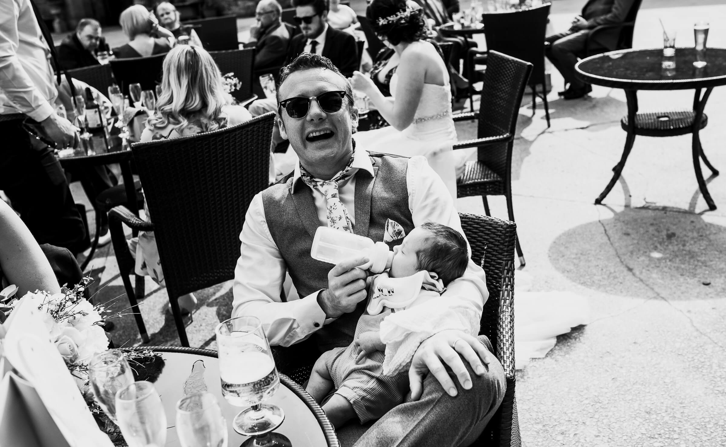 father smiling at camera while bottle feeding baby