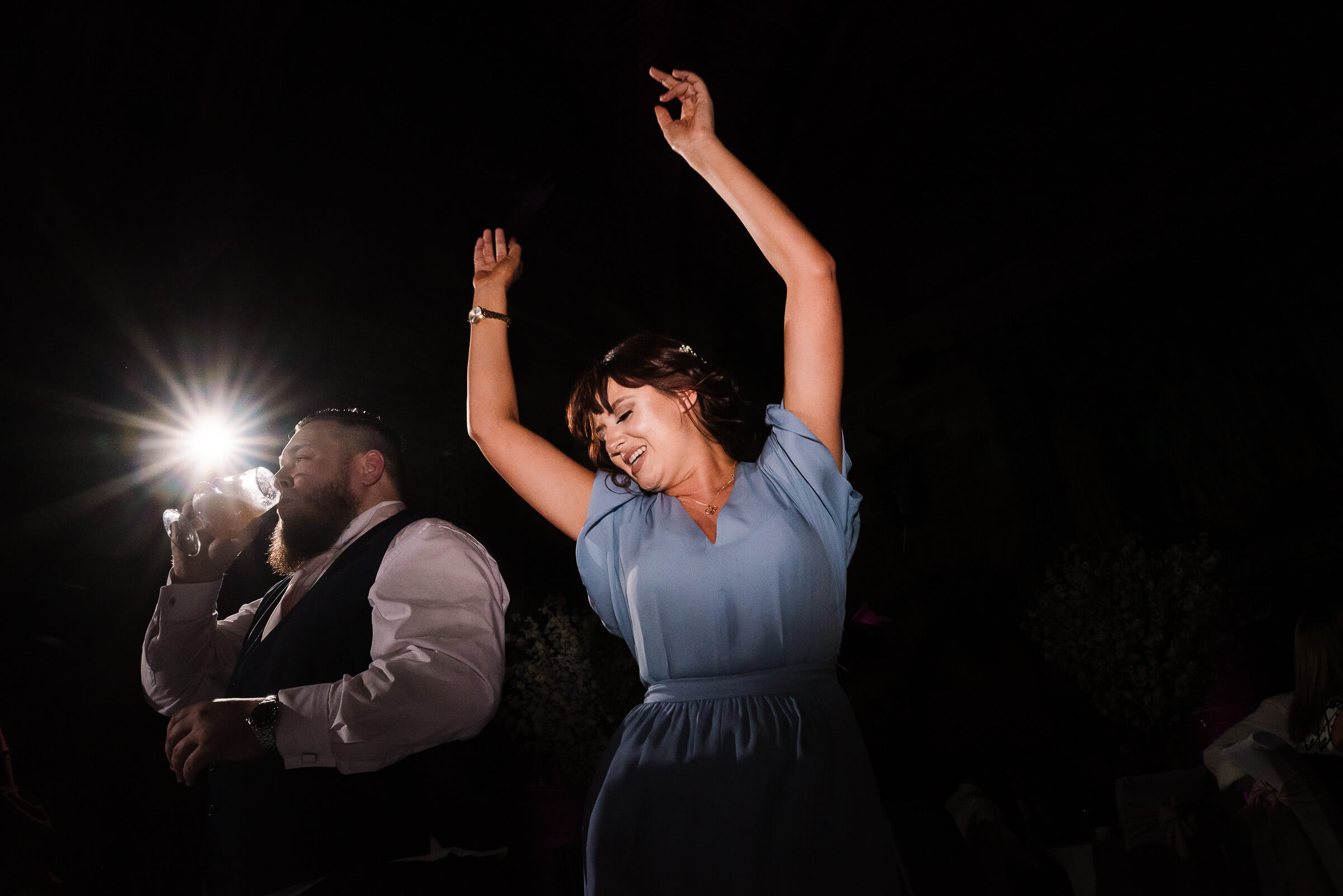 brides friend dancing with arms in the air